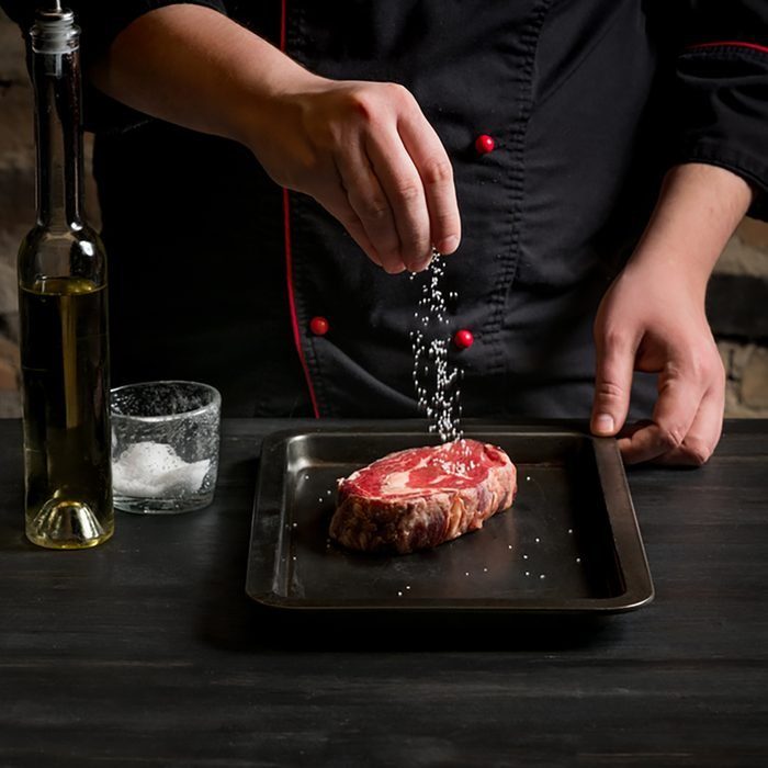 Chef salts steak grill pan. Preparing fresh beef or pork.