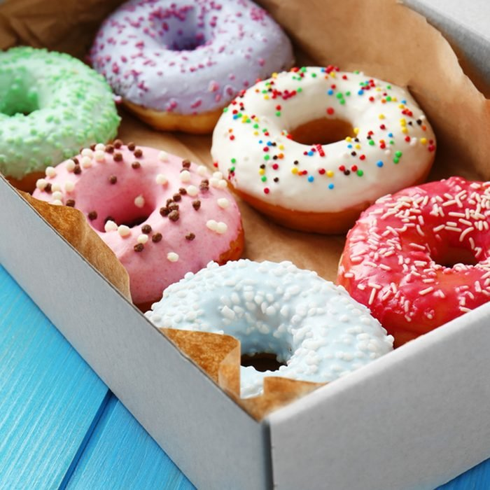 Delicious donuts in box on blue wooden background