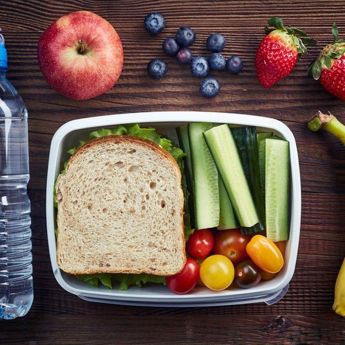 Healthy lunch box with sandwich and fresh vegetables, bottle of water and fruits on wooden background.