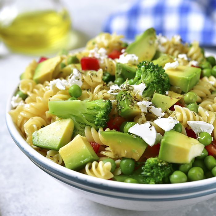 Pasta salad with green vegetables and feta in a vintage plate on a light concrete,stone or slate background.