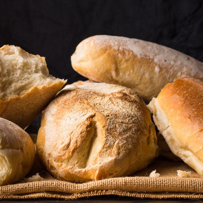Freshly baked bread loaves on burlap dark wooden background.