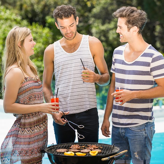 Happy friends talking to each other while preparing barbecue near pool;