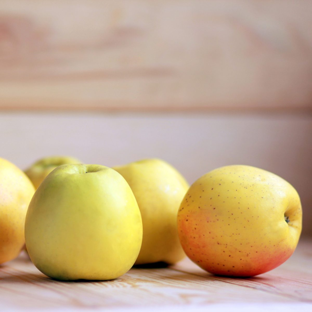 Yellow apples scattered on the wooden background.