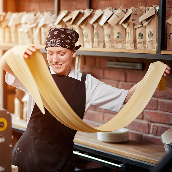 Cheerful young woman rolling a knead through pasta machine and smiling.