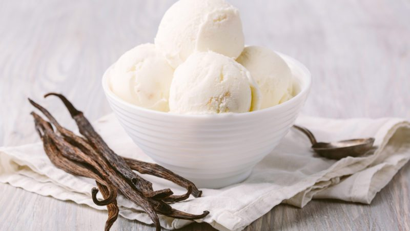 Balls of vanilla ice cream in a white bowl on a wooden background.