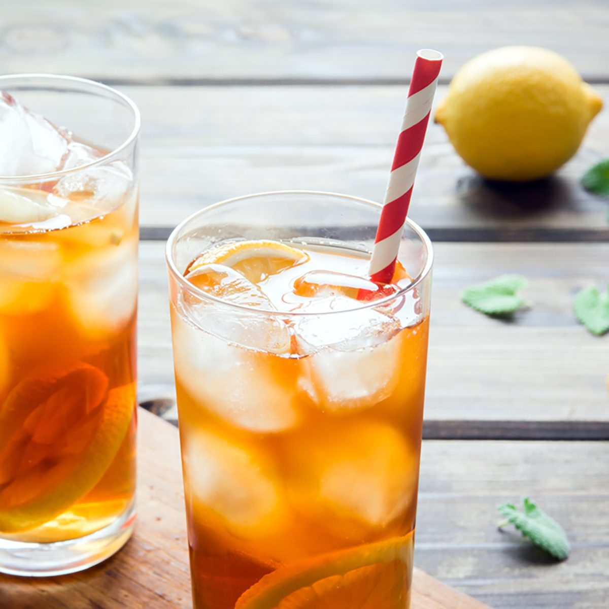 Iced tea with lemon slices, mint and ice cubes on wooden rustic background close up.
