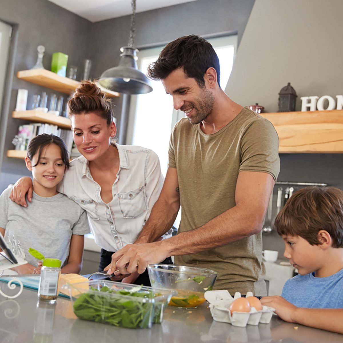 Family In Kitchen Following Recipe On Digital Tablet