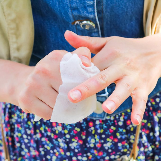 The girl wipes her hands with a napkin
