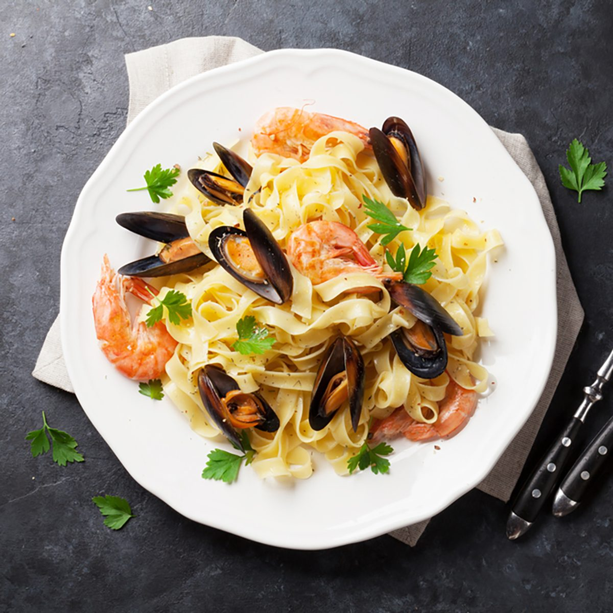Pasta with seafood and white wine on stone table. Mussels and prawns.