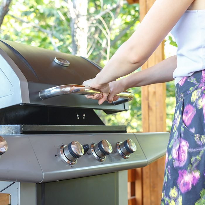 Young woman opens gas grill, prepares grill for BBQ, steak, sausages for happy family holiday.