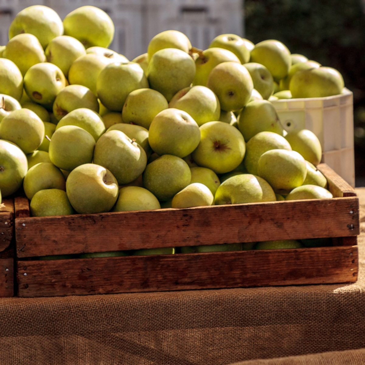 Bushel of green apples in a crate at a farmers market with other fruits and vegetables.