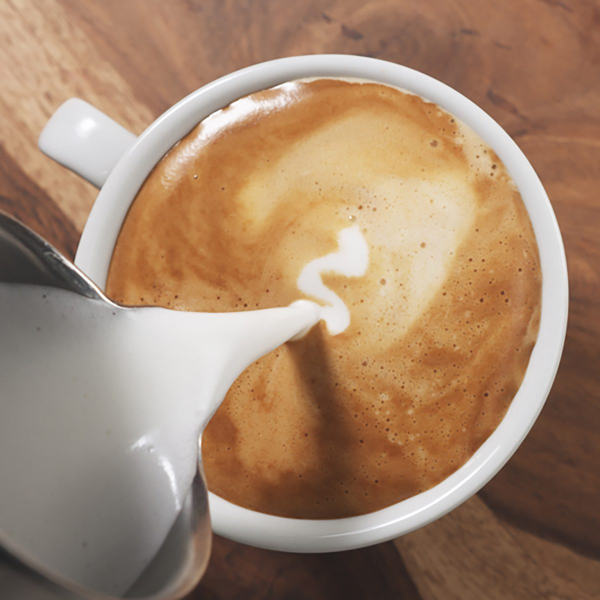top view pour steamed milk into cappuccino on wood table
