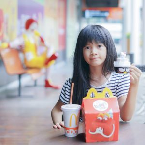 an asian girl ,in soft focus, showed her happy meal food and toy at McDonald's restaurant on October 10, 2017 in Bangkok, Thailand