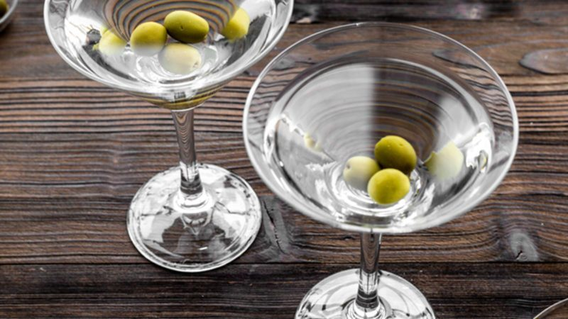 Martini cocktail in glass with olives at the bottom on dark wooden background top view.