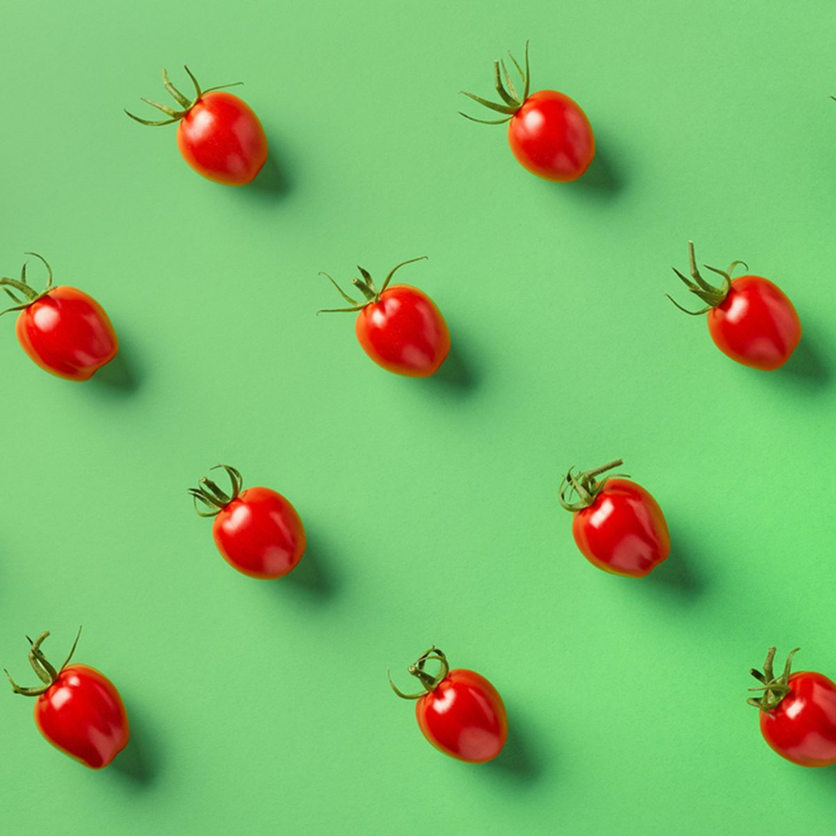 Colorful pattern of red tomatos on green background.
