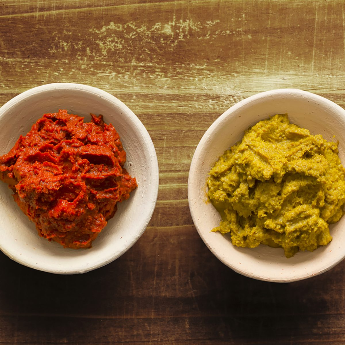 close up of bowls of rustic red and yellow indian curry paste