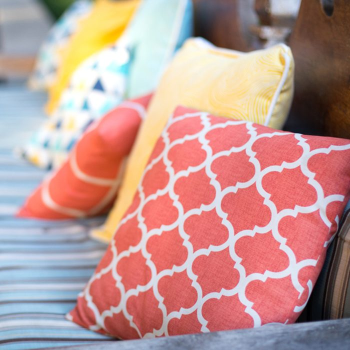 Close up on orange and yellow pattern throw pillows on an outdoor patio chair