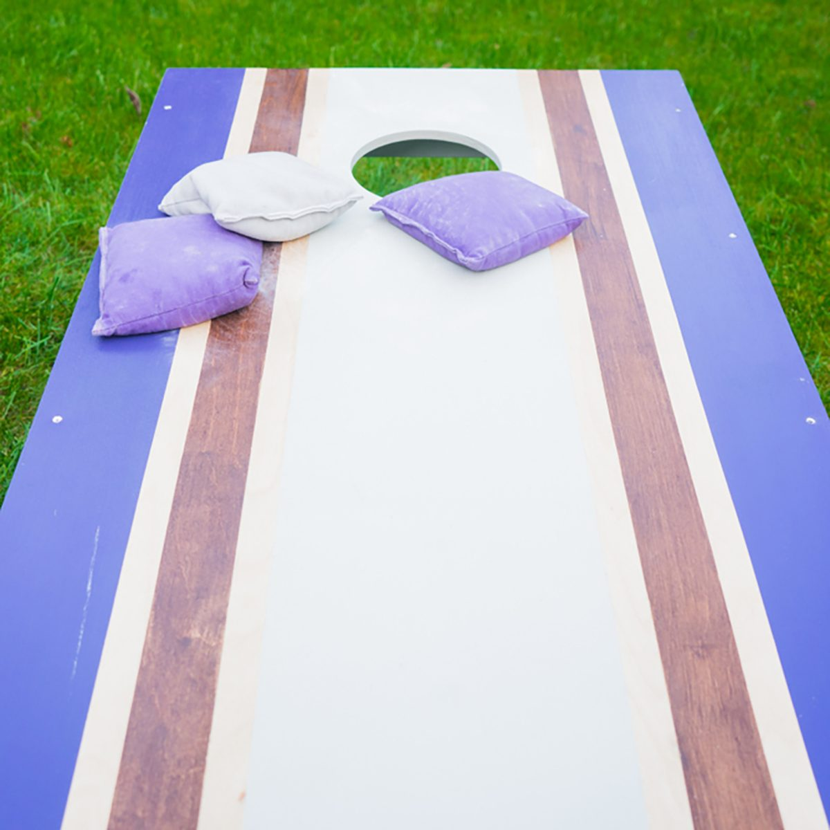 Cornhole bean bag toss wood game board outside on grass