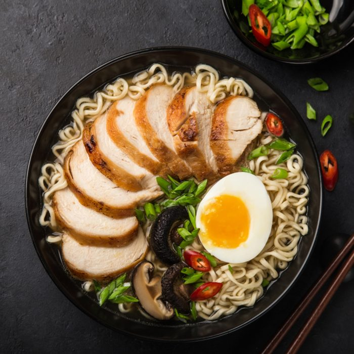 Japanese ramen noodle with chicken, shiitake mushroms and egg in black bowl