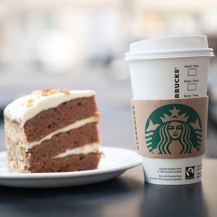 A tall Starbucks coffee in starbucks coffee shop with cake.