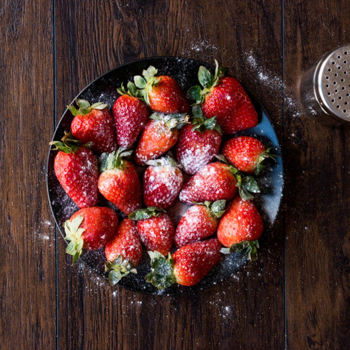 Fresh Organic Ripe Strawberries with Powdered Sugar on Black Plate.