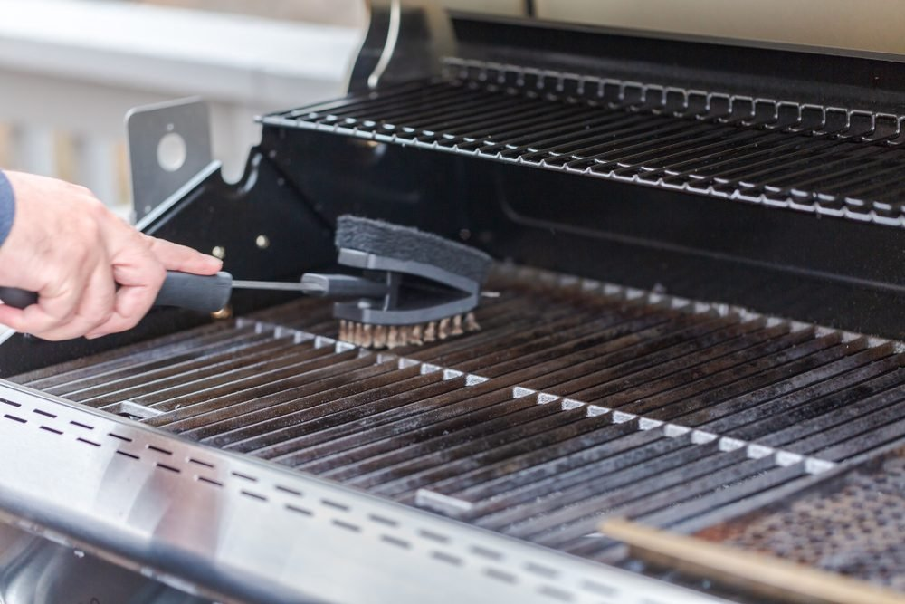 Cleaning outdoor gas grill before next grilling.; Shutterstock ID 1077948236; Job (TFH, TOH, RD, BNB, CWM, CM): TOH Wire Grill Brush