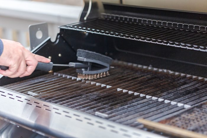 Cleaning outdoor gas grill with wire grill brush