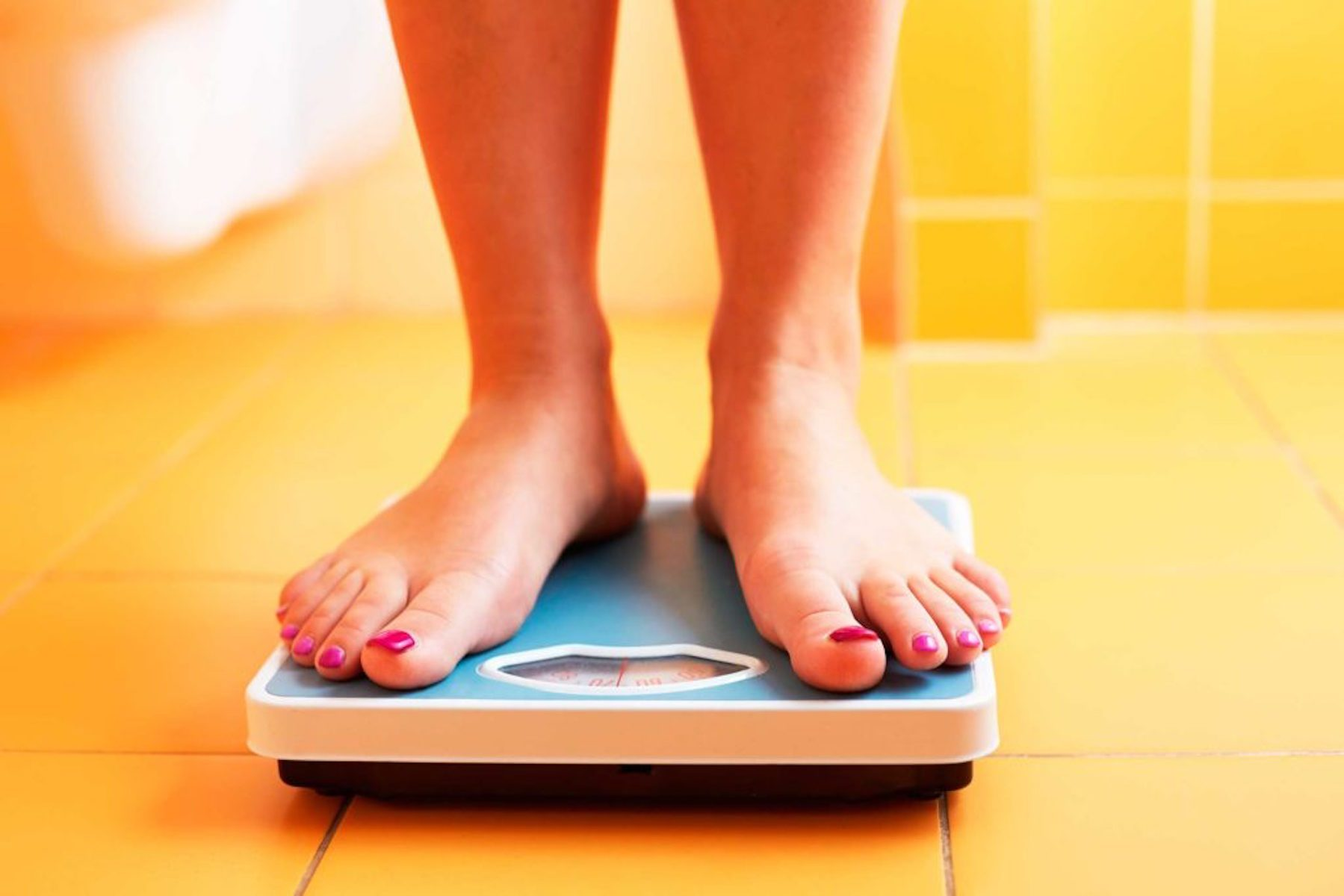 person standing on a scale, person weighing themselves