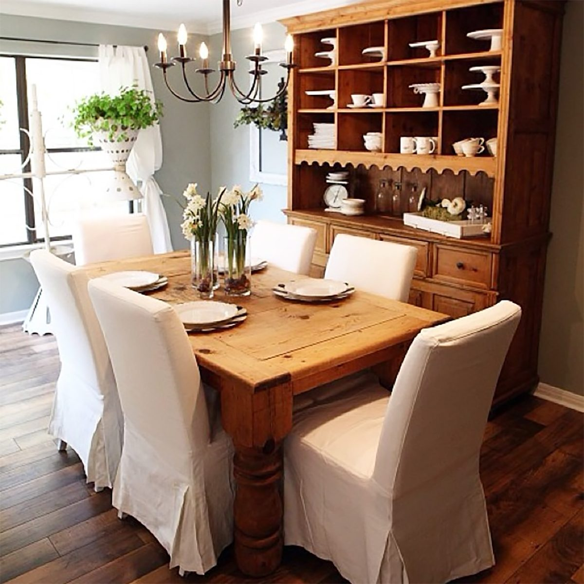 farmhouse style dining room with chairs, chandelier and storage