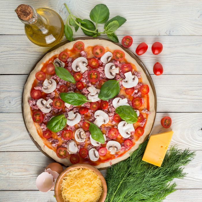 pizza on the stone for baking pizza and ingredients of pizza on a wooden background top view