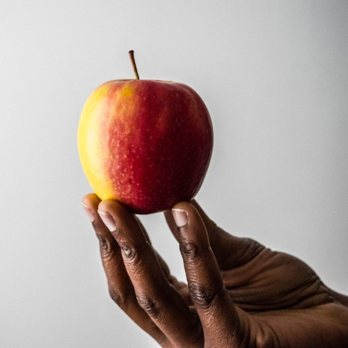 African American Woman's hand and fingers holding red pink lady apple fruit isolated on a white background in fresh and juicy color.