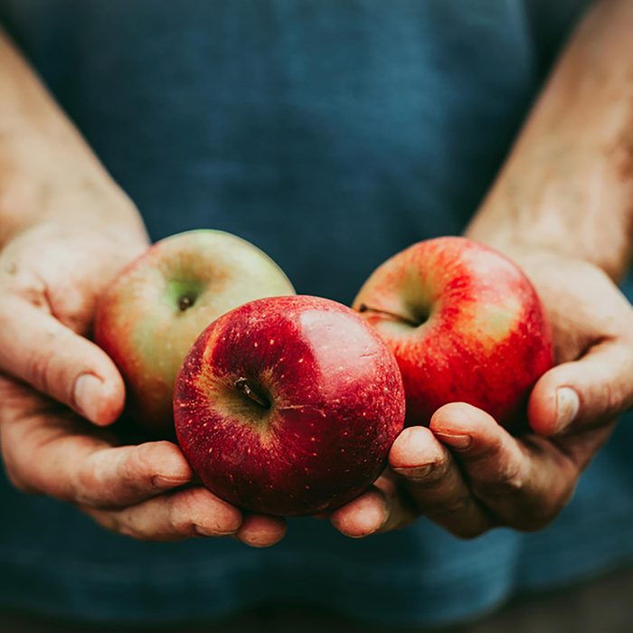 Hands holding three apples