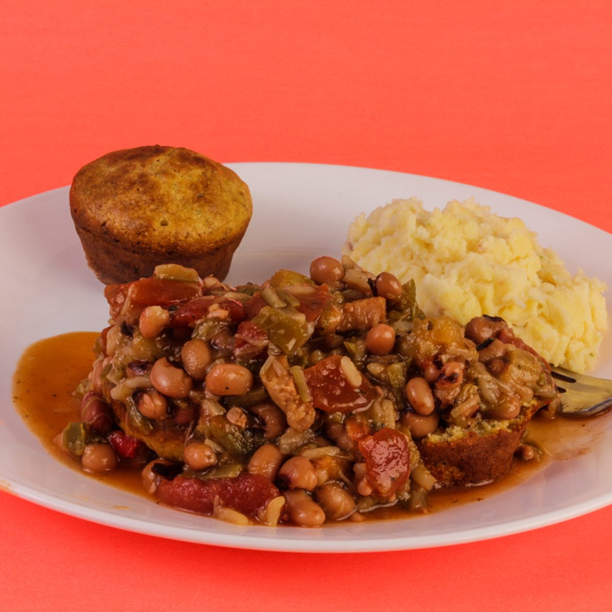Creole Chicken Gumbo on white plate with mashed potatoes and cornbread against red background.