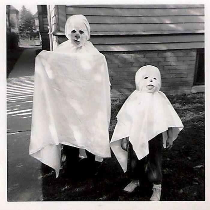children in ghost costumes on Halloween