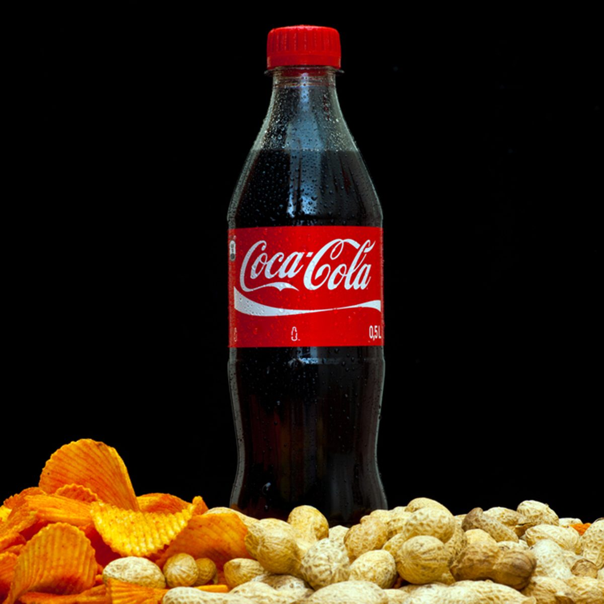 plastic bottle of soft drink coca-cola by coca-cola company on black background