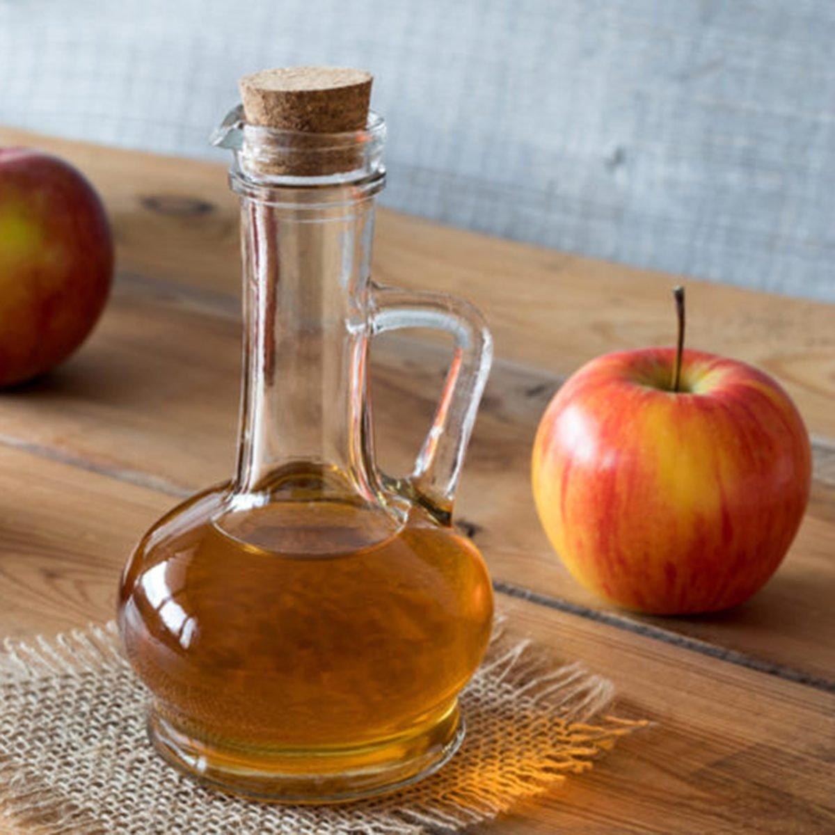 A bottle of apple cider vinegar on a wooden table