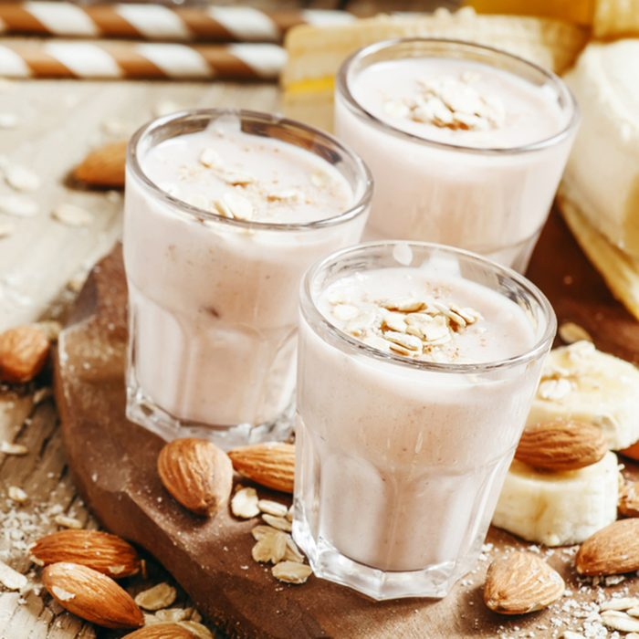 Banana smoothie with milk, oatmeal and almonds on the old wooden background