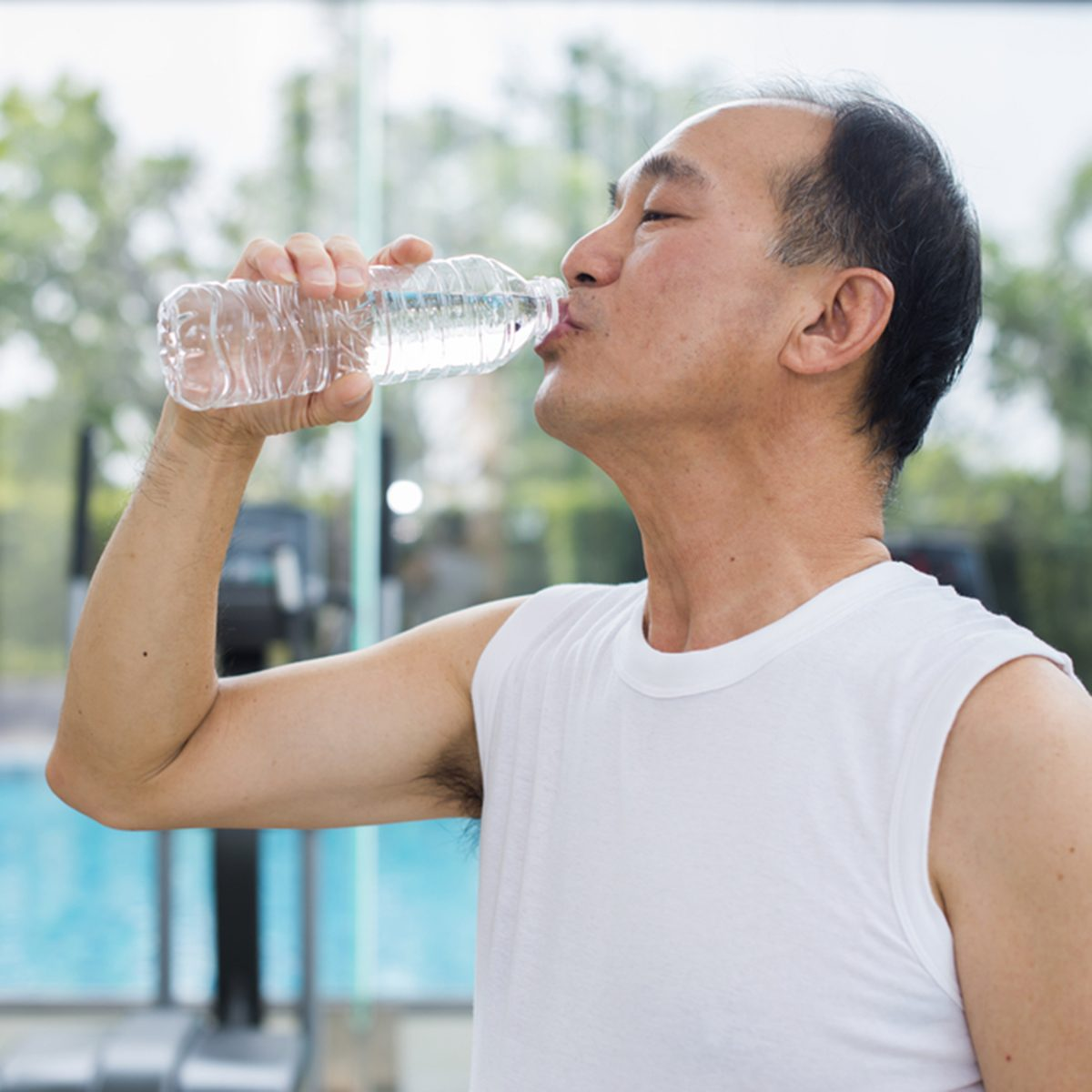 Senior asian man drinking water from a plastic bottle and background blur diverse equipment and machines at the gym room.