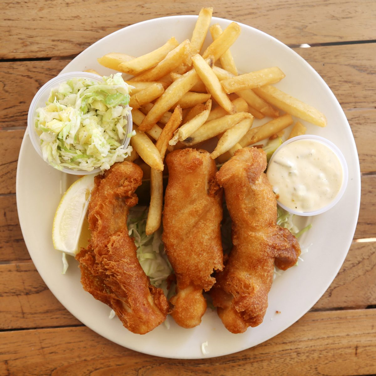 fish and chips with French fries and pineapple coleslaw on a white plate on a wooden table.