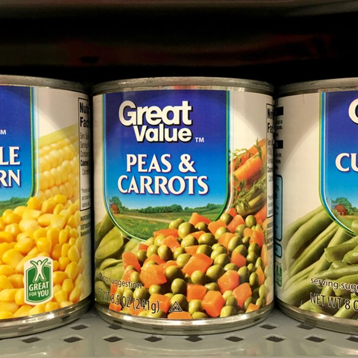 Grocery store shelf with cans of Great Value brand vegetables.