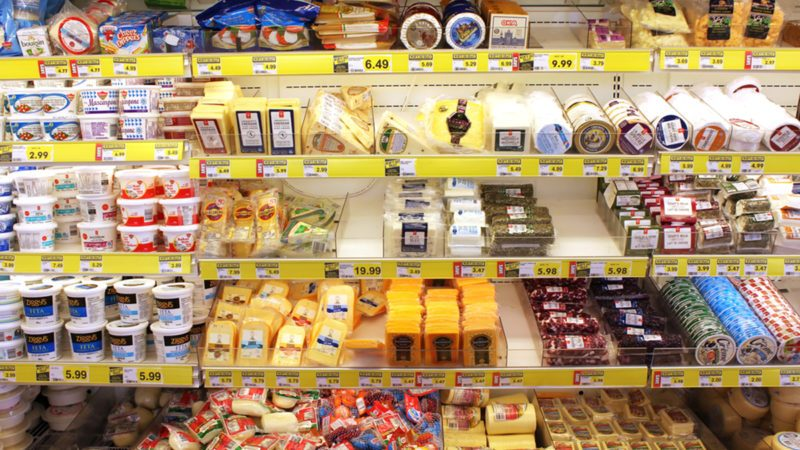 Variety of cheeses on shelves in a grocery store.