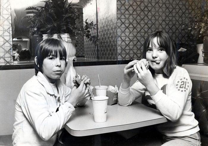 Two children eating hamburgers in McDonalds