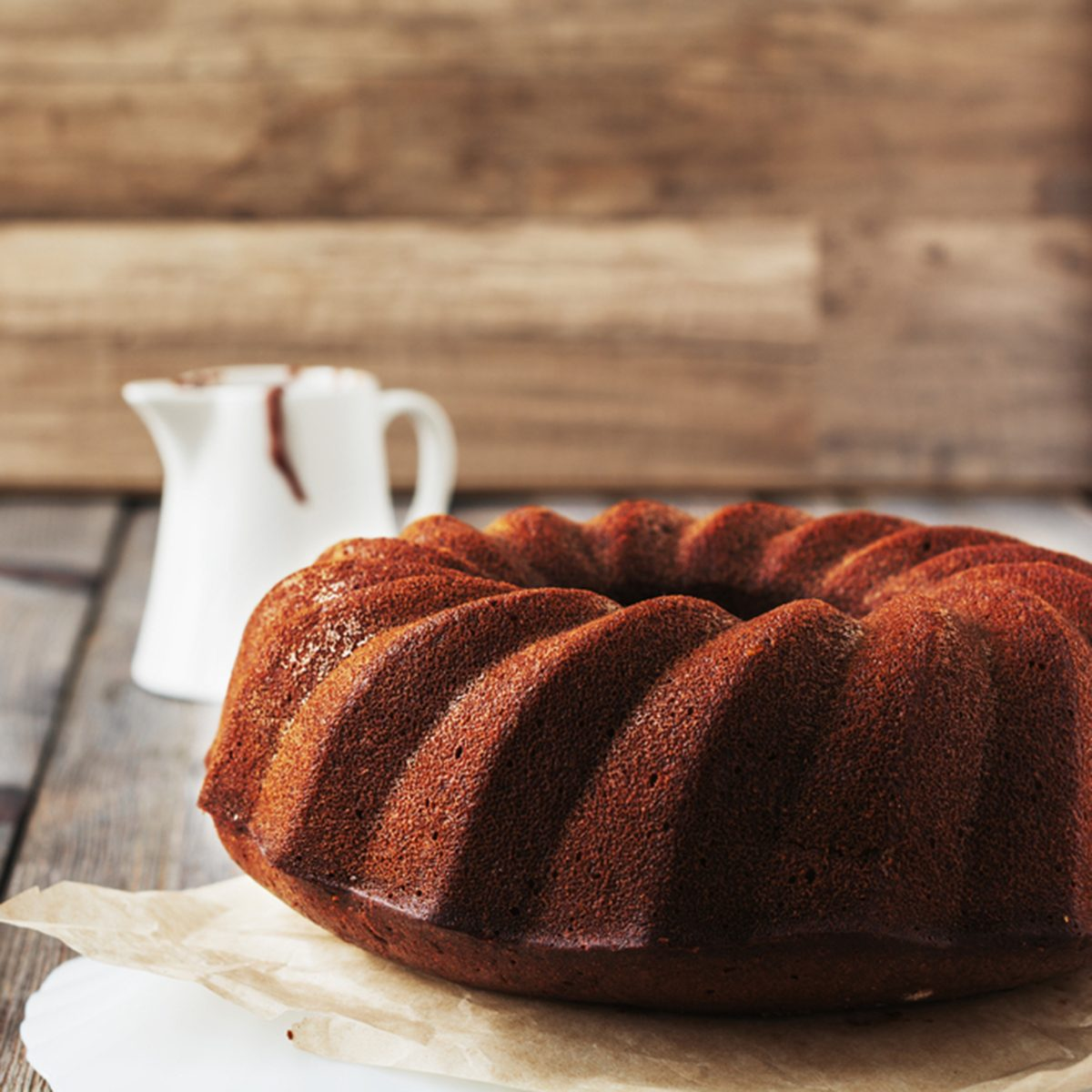 Chocolate Bundt cake with chocolate glaze on an old wooden table background.