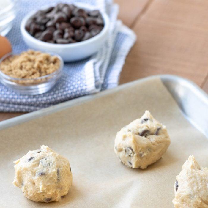 Chocolate chip cookie dough balls on a baking sheet