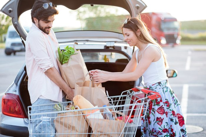 Happy young couple loading grocery bags into a car trunk at a parking lot in front of a shopping mall.
