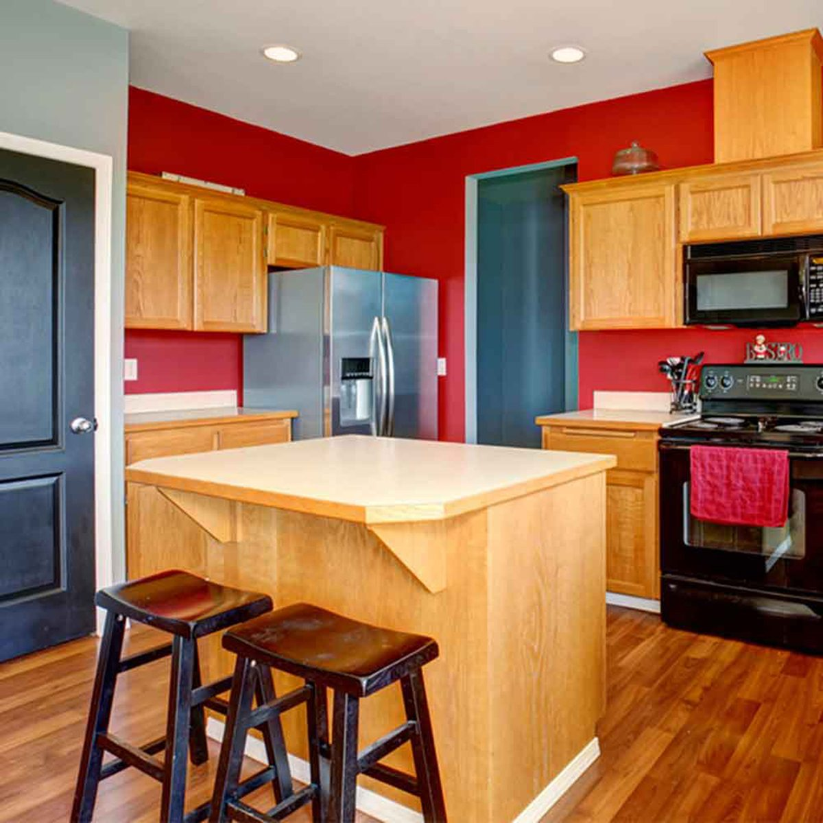 Brightly color red kitchen with a small wooden island
