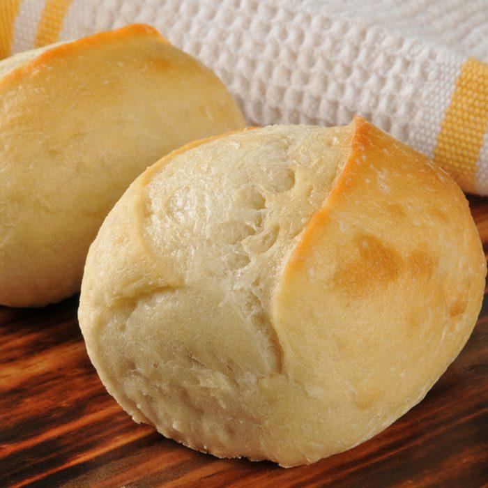 Fresh baked dinner rolls on a cutting board