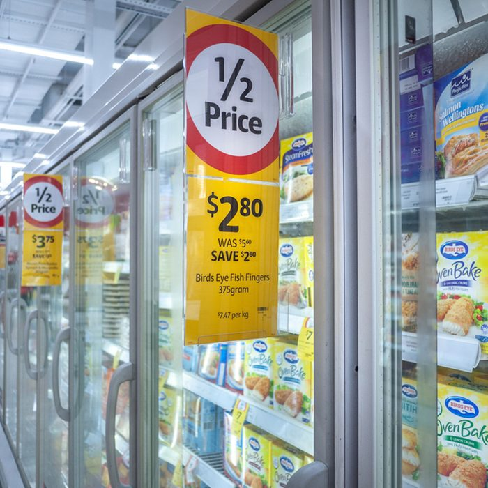 discount price tag on frozen food cabinet in Coles supermarket