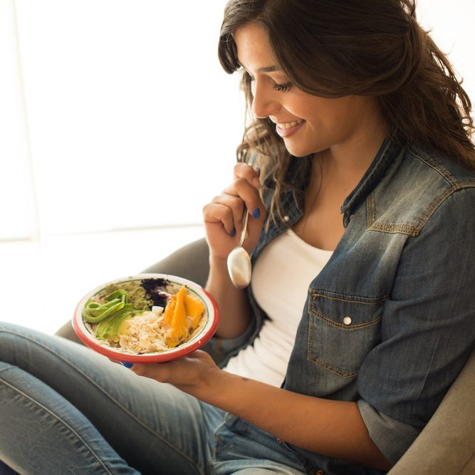 Woman eating a healthy bowl of superfoods; Shutterstock ID 724511170
