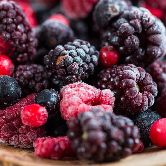 mixed frozen berries on wooden background